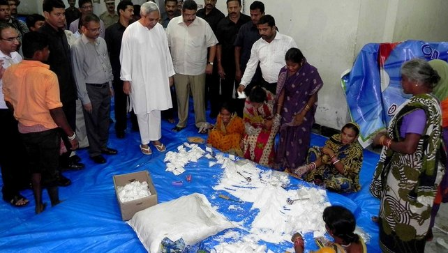 Orissa state chief minister Naveen Patnaik (fourth from left) watches as relief items are packaged for distribution to cyclone evacuees in the eastern city Bhubaneswar