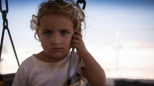 A young girl sits on a swing at the Zaatari camp