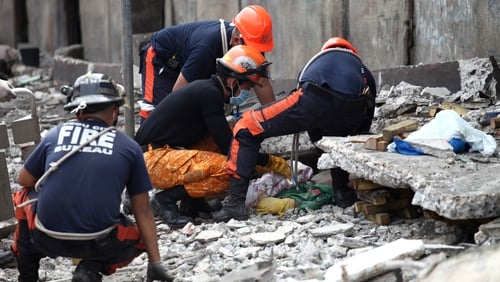 Rescuers try to uncover an unidentified man under slabs of cement in Cebu City