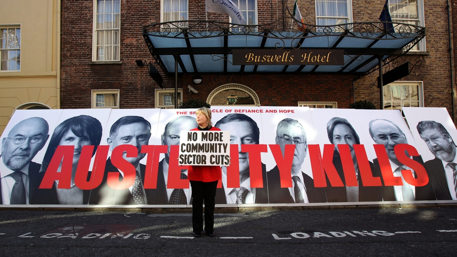 A protestor stands in front of an anti-austerity banner near Leinster House