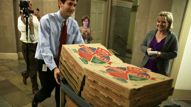A Congressional staffer brings in pizzas at the Capitol as both the Senate and House work on a deal to stop the government shutdown