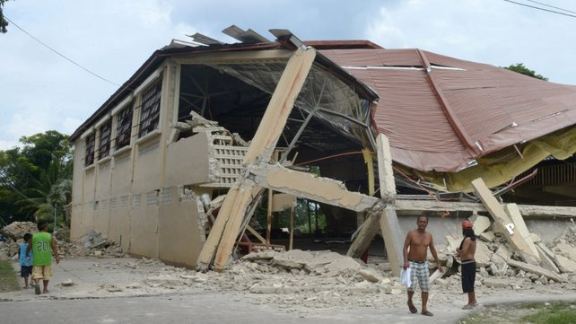 Residents walk by a damaged gymnasium on the popular tourist island of Bohol