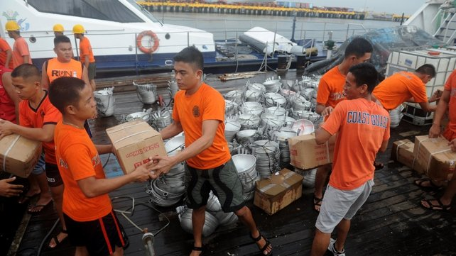 Philippine Coast Guard personnel load frying pans and relief goods onto a PCG vessel at a port in Manila