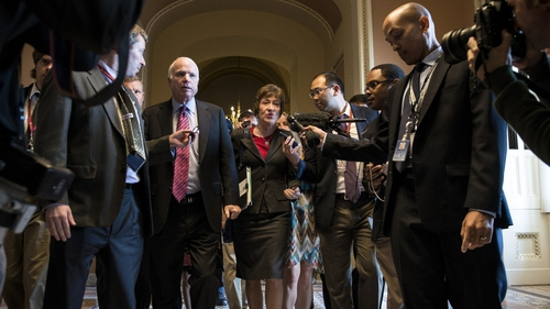 US Senators John McCain and Susan Collins talk to reporters while heading to the Senate floor
