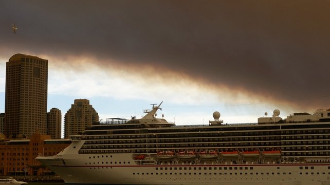 Smoke and ash from wildfires burning across New South Wales blanket a cruise ship in Sydney Harbour