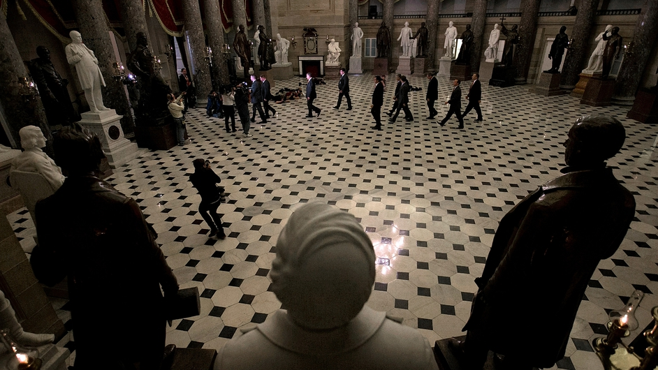 John Boehner and his entourage walk through Statuary Hall ahead of a vote aimed at ending the US shutdown