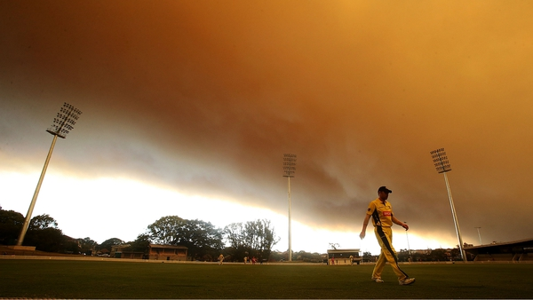 Smoke billows in the background of a cricket match at Drummoyne Oval, north of Sydney