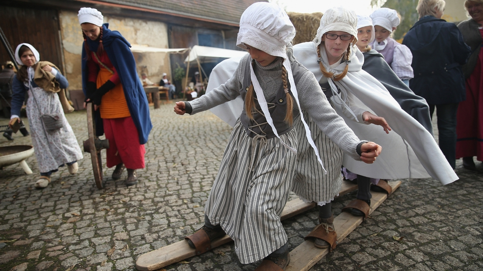 Local children dressed in early-19th century regional period clothing play games in a recreated 1813 village in Liebertwolkwitz district in Germany