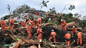 Policemen search for missing people after a landslide on Oshima island, 120km south of Tokyo