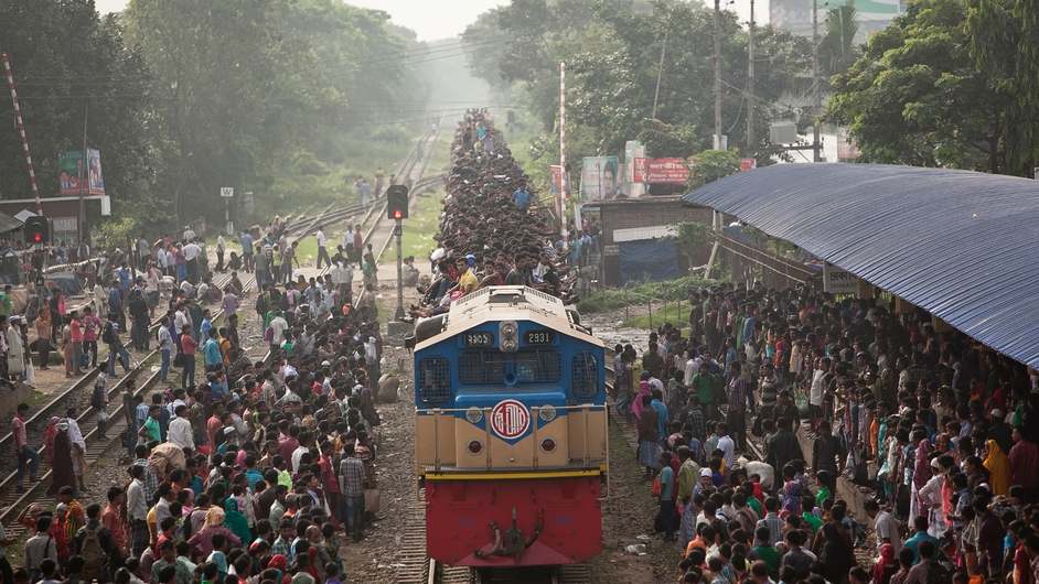 People ride an overflowing train at a railway station in Dhaka in Bangladesh