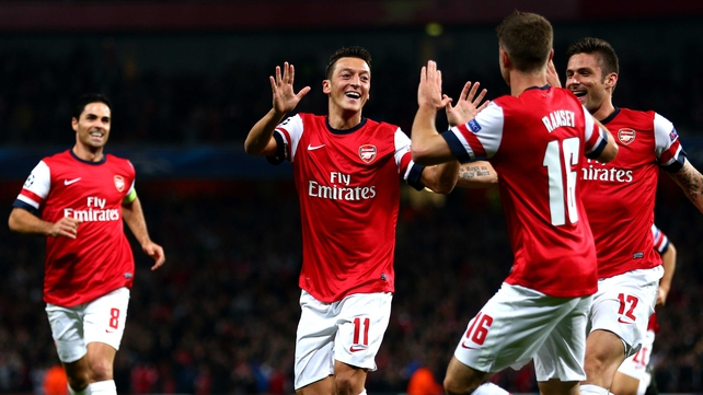 Mesut Ozil is mobbed after scoring against Napoli in the Champions League