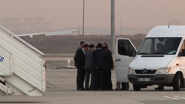 Some of the hostages wait to board a plane after their release