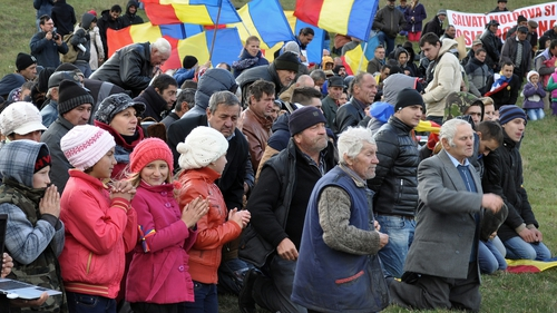 Protesters kneel to pray during an anti-fracking protest in Silistea village in Romania