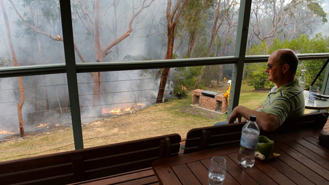 Local resident Paul Chester watches the containment fires from the balcony on his house at Faulconbridge