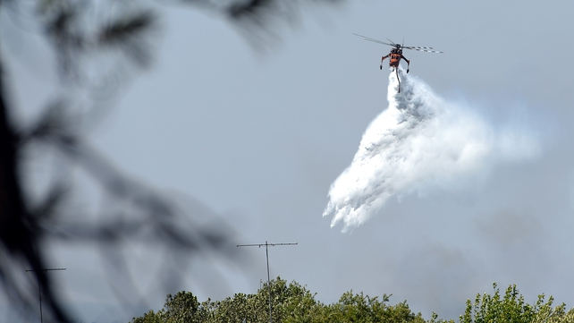 A helicopter drops water to douse bushfires along the Linksview Road near Faulconbridge in the Blue Mountains