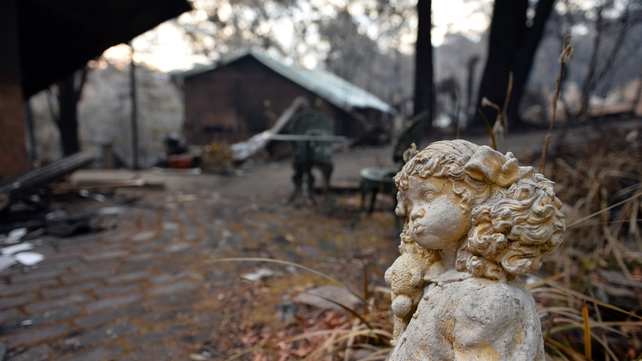 A statue stands outside a burnt out home in Winmalee in the Blue Mountains