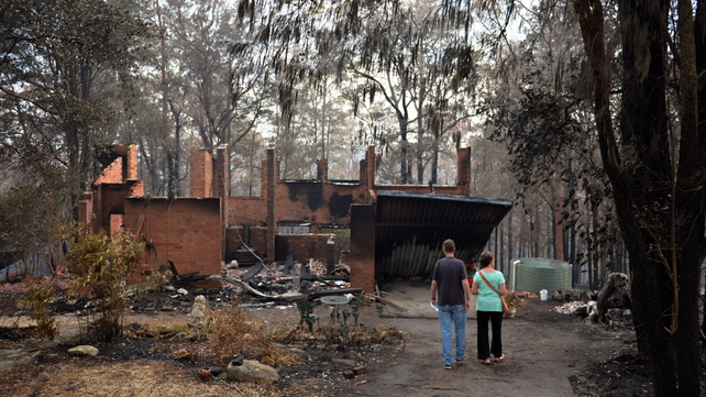 Jennifer Schweinsberg and her son David view the blackened structured of her home at Winmalee