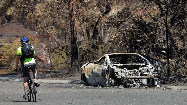 A cyclist passes by a burnt-out car in Springwood in the Blue Mountains