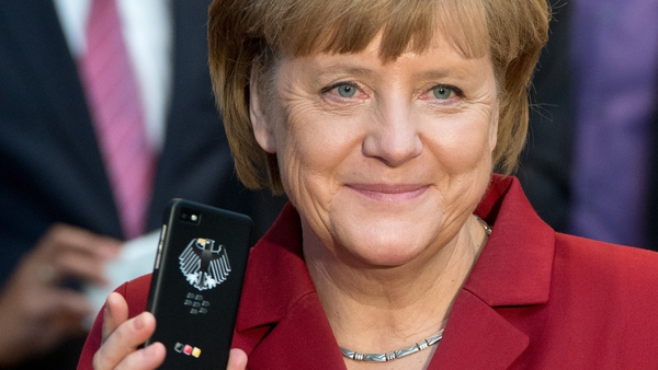 German Chancellor Angela Merkel holding a tapping proof BlackBerry mobile device in March of this year