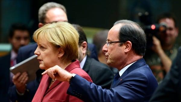 French President Francois Hollande  talks with German Chancellor Angela Merkel