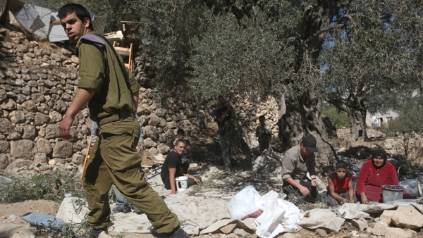 The Israel army guards Palestinian farmers from attacks by Jewish settlers from the nearby Israeli settlement of Tal Rumeda near the West Bank city of Hebron