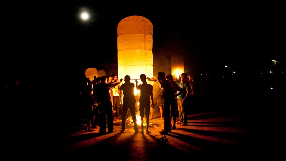 Buddhists light a large paper balloon into the sky during Probarona Purnima in Ramu, Bangladesh