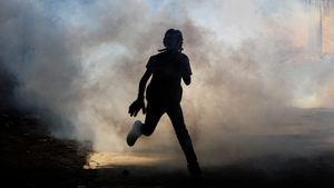 A Palestinian protester runs to seek cover from tear gas fired by Israeli soldiers