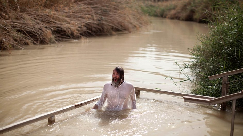 A Russian Orthodox pilgrim enters the water on the West Bank side of the Jordan River for the baptismal ceremony at the site known as Qasr el-Yahud
