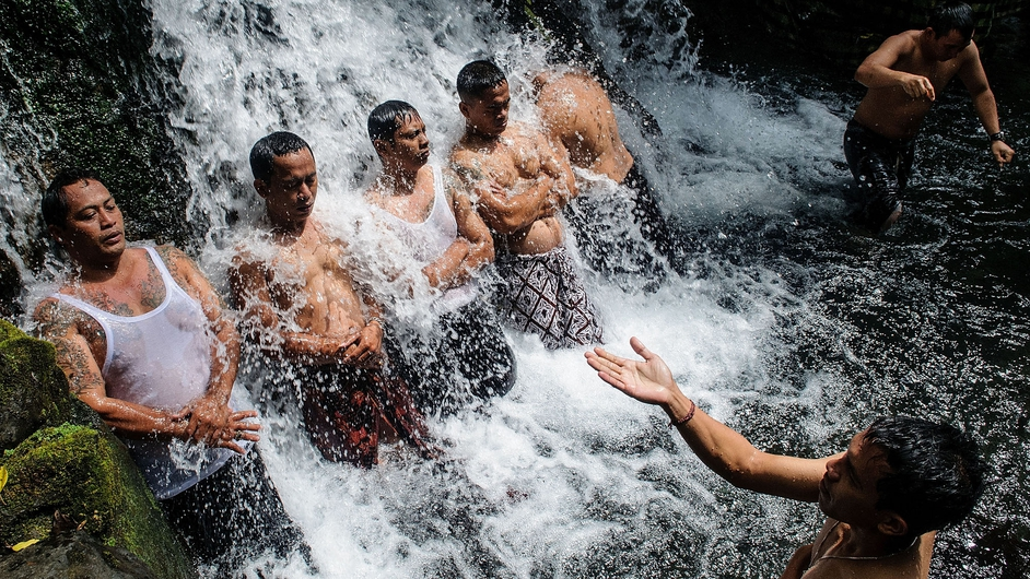 Balinese Hindu devotees bathe as they perform the 'Melukat' ritual during full moon at Sebatu holy Waterfall
