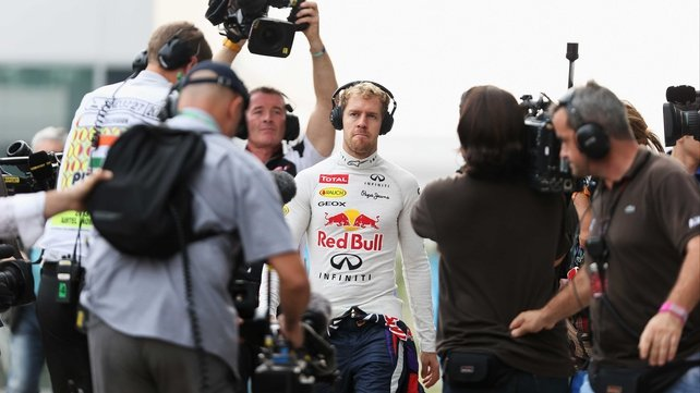 Sebastian Vettel is followed by camera crews on his way to his team garage during qualifying