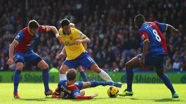 Mesut Oezil of Arsenal is challenged by Barry Bannan (c), Joel Ward (l) and Kagisho Dikgacoi of Crystal Palace