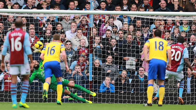 Everton goalkeeper Tim Howard saves a penalty from Aston Villa's Christian Benteke (r)