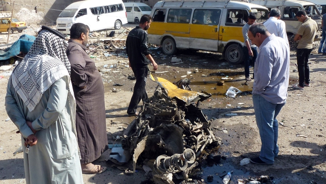 Iraqis look at the remains of a vehicle following an explosion in the the Mashtal district