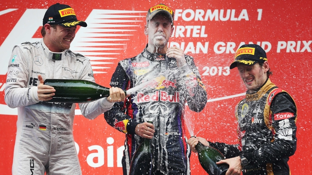 Sebastian Vettel is champagne-soaked by Nico Rosberg (L) third placed Romain Grosjean (R)