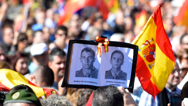 People hold Spanish flags and portrait of victims of terrorism at Plaza de Colon