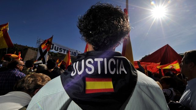 A man with a scarf with a Spanish flag and reading 'Justice' as he gathers with thousands of protesters