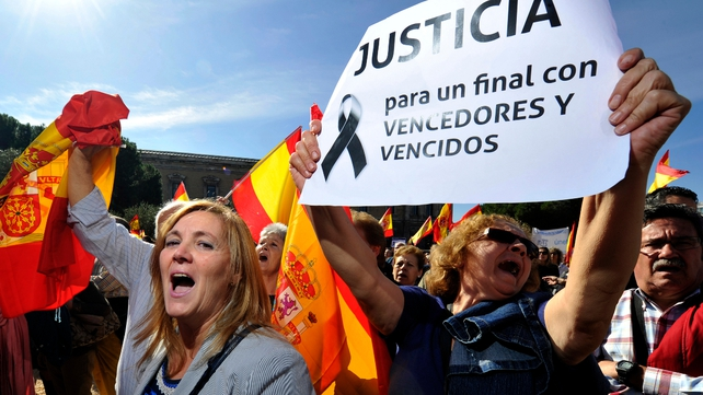 People brandish Spanish flags and a poster reading 'Justice, for an end with winners and losers'