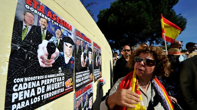 A woman looks at posters against ETA and the Spanish government during the gathering at Plaza de Colon