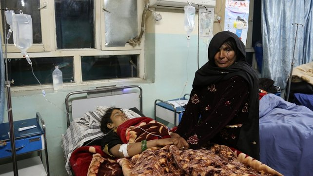 A woman holds the hands of a victim of the roadside bomb in hospital