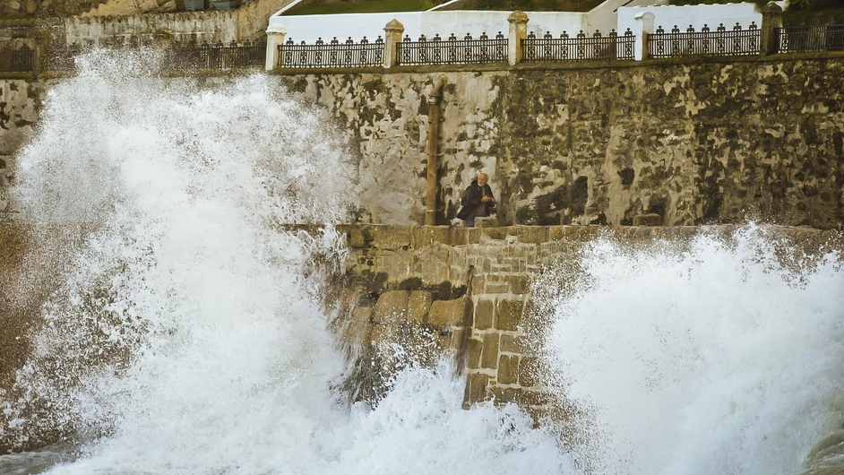 A man looks on as waves crash over a pier in Cornwall, England