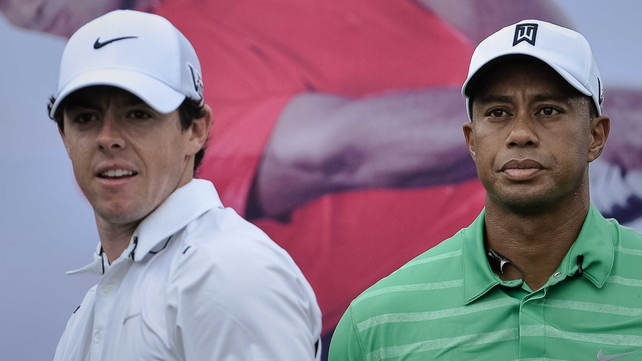 Rory McIlroy and Tiger Woods look on during their one-on-one golf match-up