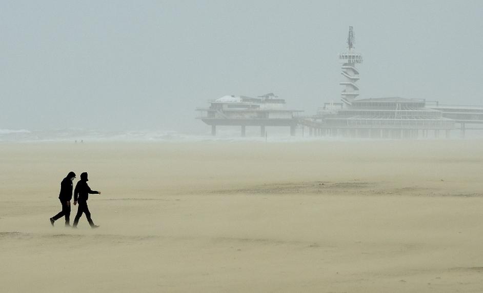 Hikers walk during the storm on the beach of Scheveningen, Netherlands