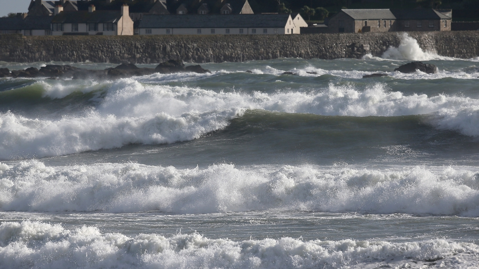 Waves roll in front of St Michael's at Marazion near Penzance, England