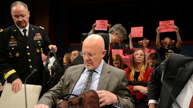 Protesters in the room held signs that said 'stop spying on us'