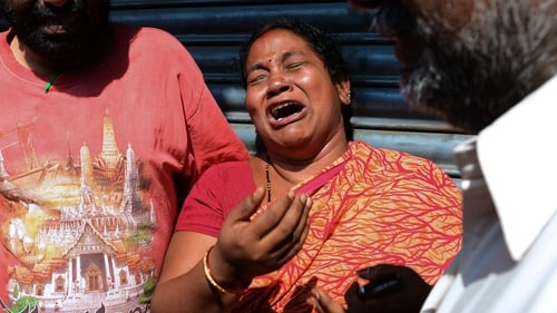 Relatives of those killed in a bus accident react after receiving news from police