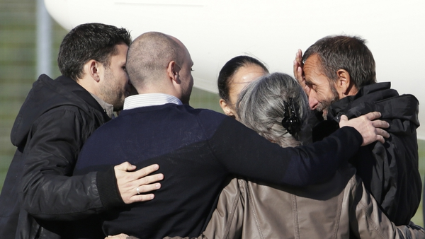 Former French hostage Daniel Larribe (R) is welcomed by his family at Villacoublay