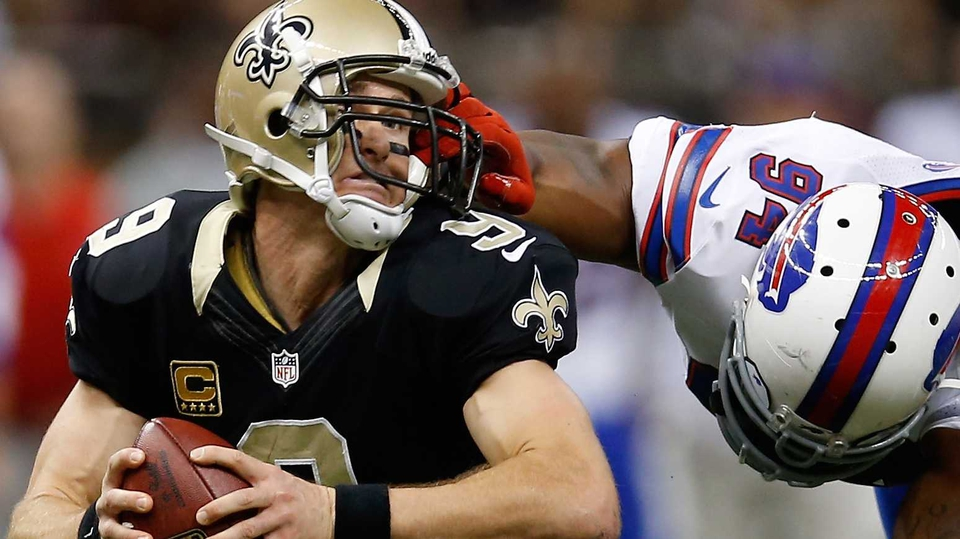 Drew Brees of the New Orleans Saints is pulled by the facemask by Mario Williams of the Buffalo Bills at Mercedes-Benz Superdome