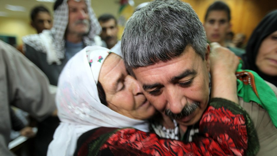 Palestinian prisoner Najeh Meqbel is welcomed by his mother after being released from an Israeli prison as part of revived Israeli-Palestinian peace negotiations