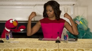 US First Lady Michelle Obama flexes her muscles alongside Sesame Street characters Elmo and Rosita
