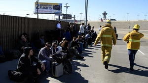People sit outside awaiting clearance to re-enter the airport